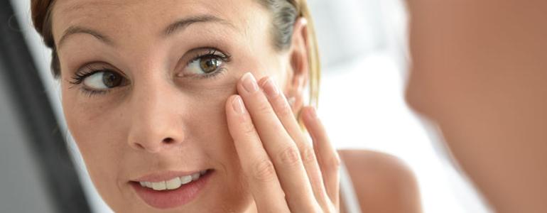 mujer echándose crema en la zona de los ojos